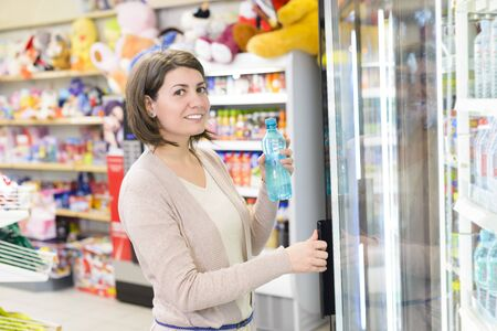 frig: Young woman holding  a bottle of water for buying it from a store