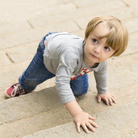 climbing stairs: Cute boy climbing on stairs Stock Photo