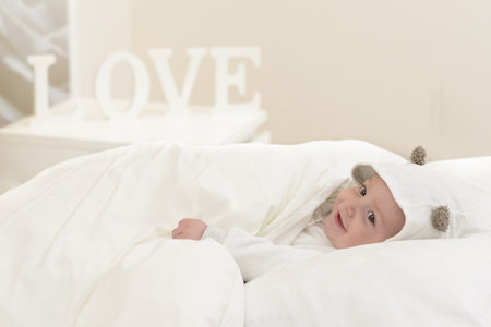 baby sleep: Happy baby in bed prepared for sleep, Love word in background.