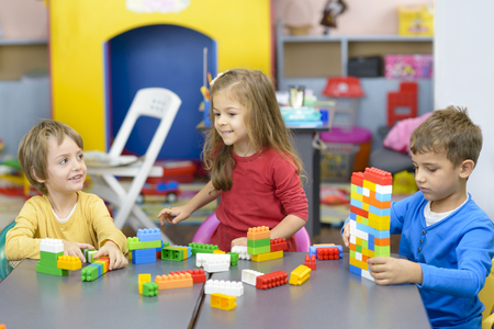 Three happy kids playing with plastic building blocks at kindergarten