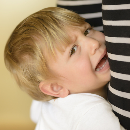 Little boy crying and holding mother legs