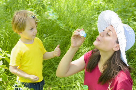 Beautiful young mother playing with her son in grass using bubble blower