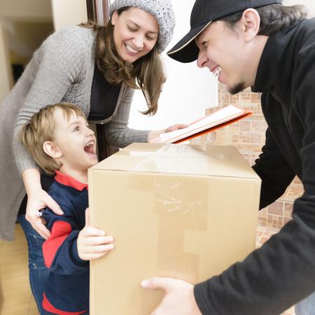 Koerier die een pakket levert aan een gelukkige jongen