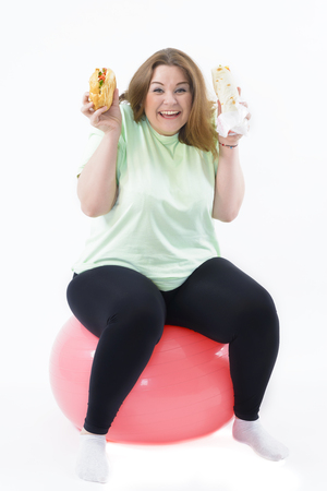 corpulent: Corpulent woman having addiction to unhealthy food sitting on fitness ball Stock Photo