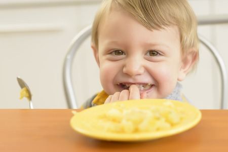 mashed potatoes: Cute little boy eating and smiling in the kitchen