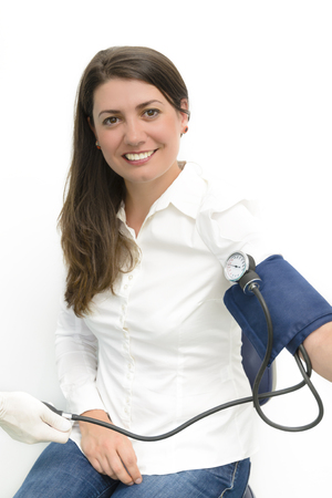 systolic: Beautiful young woman using blood pressure measurement device sphygmomanometer