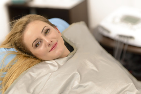 Mooie jonge vrouw krijgt thermische deken behandeling bij schoonheidssalon