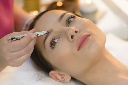 Attractive woman getting tweezing procedure at beauty salon