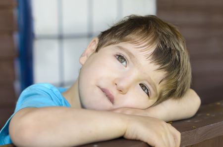 waiting glance: A wistful child on his porch Stock Photo