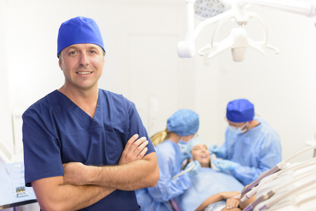 Portrait of happy male dentist and his team at clinic