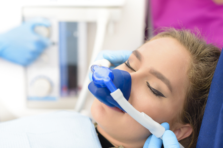 dentist mask: Beautiful getting woman inhalation sedation at dental clinic