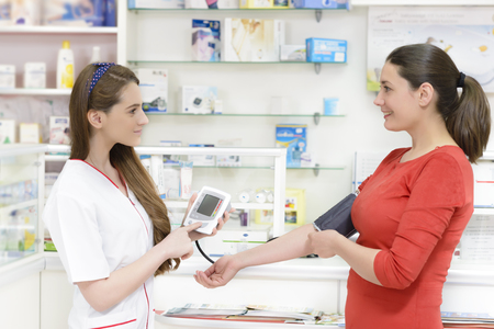 Pharmacist showing a digital blood pressure measurement device to a customer
