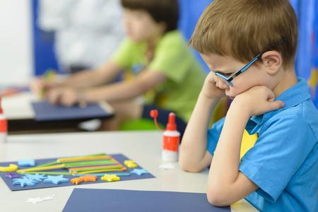 Boos kind kijkt naar zijn vak bij de kleuterschool Stockfoto - 79008926