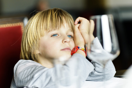 A serious child sitting alone at table in a restaurant Stock Photo