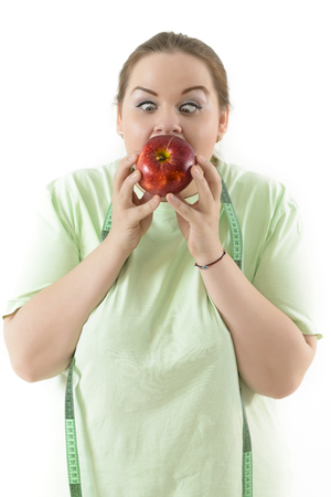 Corpulent woman struggle to eat healthy biting an apple.