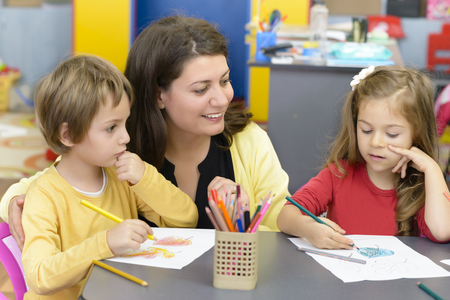 Kids drawing at kindergarten being supervised by educator Stock Photo