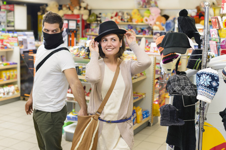 Thief stealing from handbag of a woman trying a hat  in a store Stock Photo
