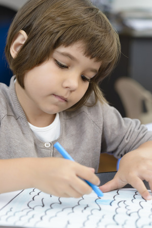 Lonely Girl drawing at kindergarten Stock Photo