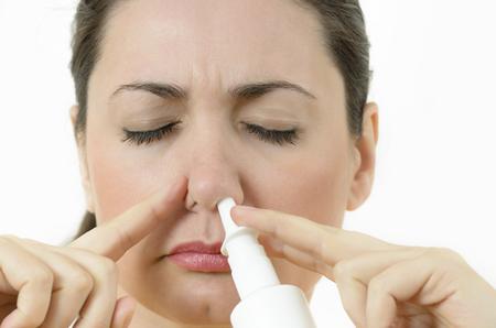 Een jonge vrouw die neusspray gebruikt, die het neusgat bedekt Stockfoto