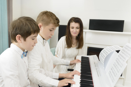Kids studying at electric piano instrument, playing in tandem, teacher next to them
