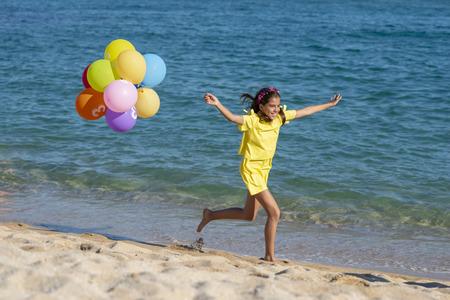 Happy girl holding balloons running on beach, summer day Stock Photo