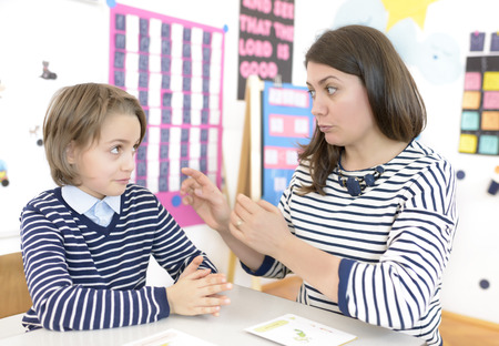 Cute boy and young woman speech therapist during private language lesson at office Stock Photo