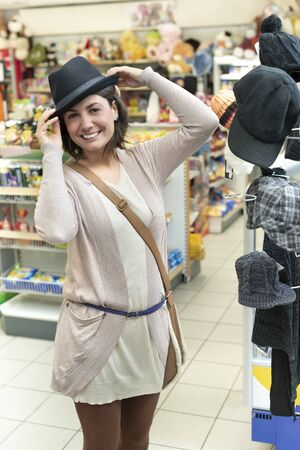 Happy woman trying a hat  in a store
