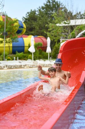 Father and son on a water slide in the water park in a summer day