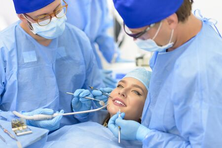 Dentist doctor and his team treating a patient at clinic Stock Photo