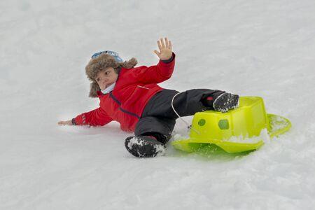 Cute kid enjoying winter time falling, from sledge