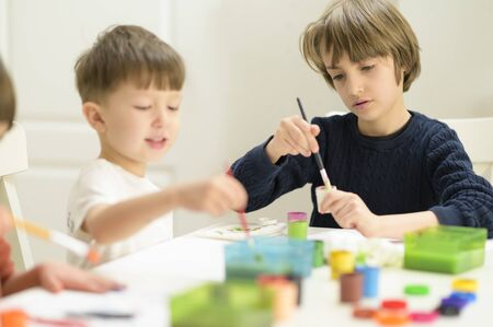 Cute funny kids doing their craft, painting at kindergarten Standard-Bild