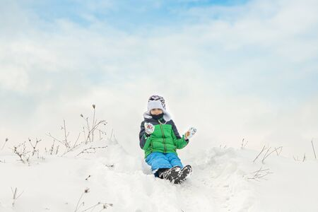 Cute kid enjoying winter time playing with snow