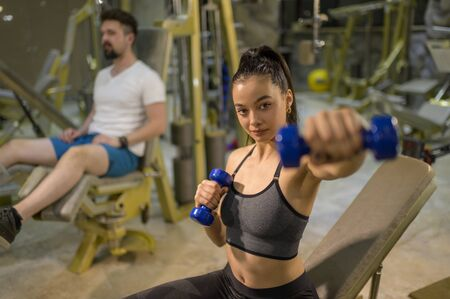 People Working Out at gym attractive young woman working out with dumbbells at a gym Standard-Bild