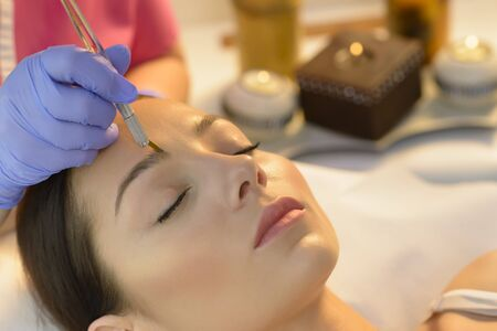 Attractive woman getting permanent makeup eyebrows procedure at beauty salon. Mikrobleyding eyebrows workflow in a beauty salon in a romantic environment. Cosmetologist applying a special permanent makeup on a woman's eyebrows