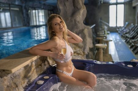 Attractive sensual woman relaxing in jacuzzi holding a champagne glass Standard-Bild