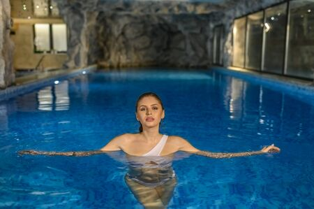 Attractive sensual woman relaxing in pool in a touristic resort