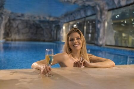 Attractive sensual woman relaxing in a pool in a touristic resort holding a refreshing drink glass
