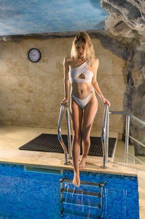 Attractive graceful sensual woman entering in pool in a touristic resort Standard-Bild