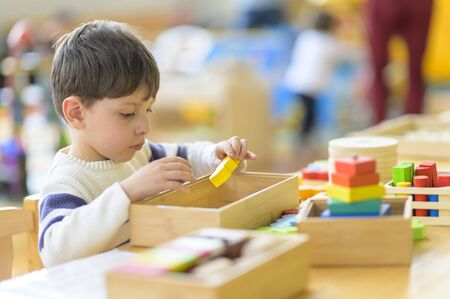 Cute little boy playing alone at kindergarten with construction toy
