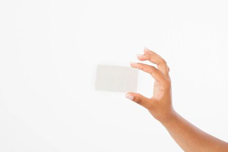 hand hold blank business card. female arm hold paper isolated on white background. copy space. mock up.