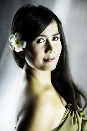 Beautiful Asian woman with a frangipani flower in her hair. This image was made with a Nikon D800 full frame camera and Nikon 105mm prime lens. Stock Photo
