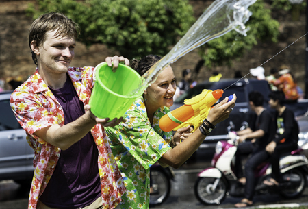 A couple with a bucket and a water gun enjoy the Song Khran Festival in Chiang Mai, Thailand.  This is the traditional new year in Thailand where Chiang Mai has the reputation for the biggest celebrations. Many tourists come to the city from around the co