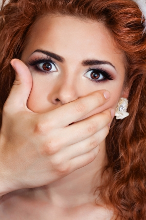 hand shutting the mouth of the girl  and she look scared Stock Photo - 14635349