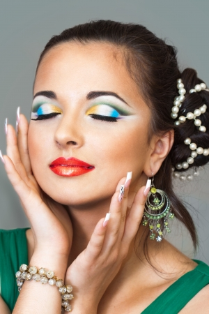 artist's model: pretty brunette smiling and having an oriental makeup  Stock Photo