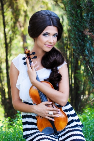 A portraite or a pretty violonist in the park