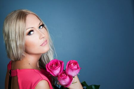Blond girl holding three pink roses photo