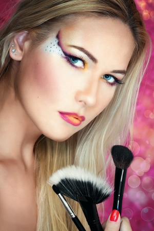 Close up portrait of a blonde girl holding brushes  photo