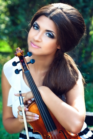 A portraite or a pretty violinist in the park  photo