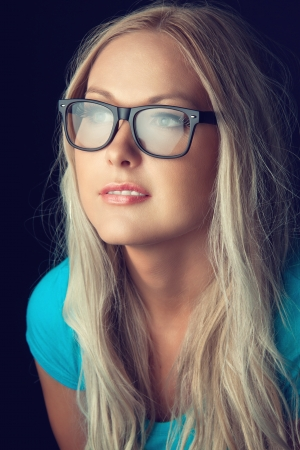 Blonde girl wearing glasses and looking aside