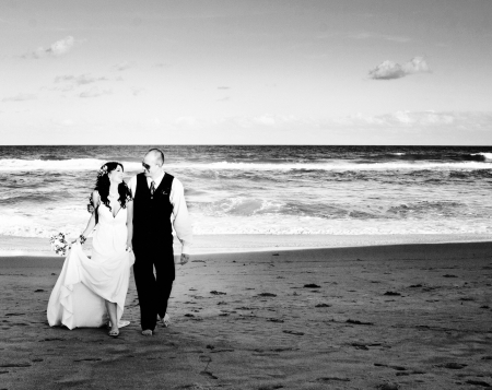 Bride and groom looking happy on the beach  photo